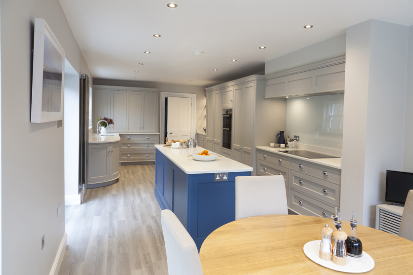 Long French Grey Grove kitchen, counter tops are Bianca Massa quartz with a Pitch Blue island complimenting the beech wood floor.